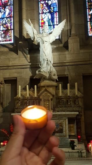 在大天使麥可前點蠟燭祈禱